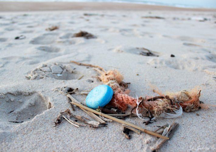 Praia com lixo, desde corda das redes dos pescadores a tampas de garrafas.